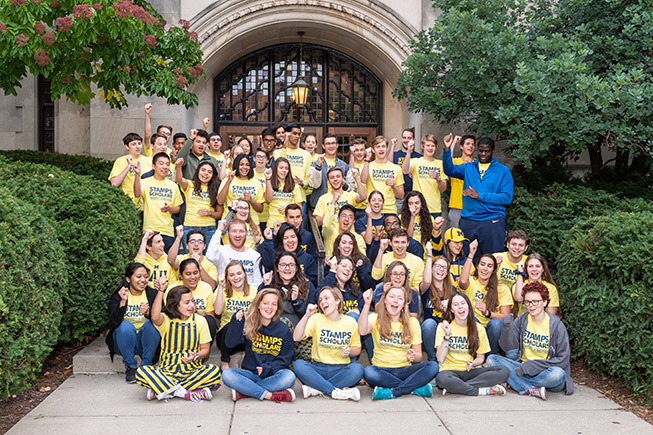 55 Stamps Scholars with fists raised while singing the Michigan Fight Song