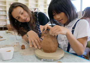 Student from Stamps School of Art and Design helping a Japanese girl on a pottery wheel